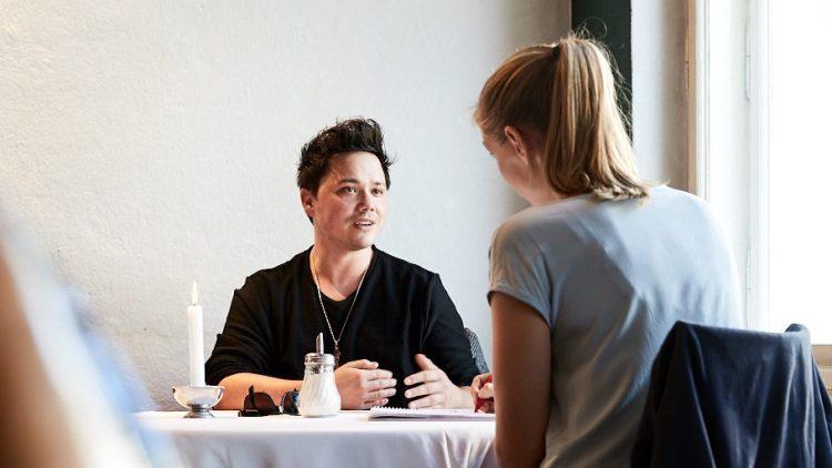 Patric Scott mit QIEZ Redakteurin an einem Tisch im Schwarzen Cafe in Berlin.