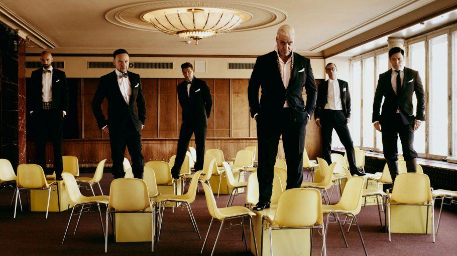 Die Rammstein-Musiker stehen auf gelben Stühlen in einem Foyer.