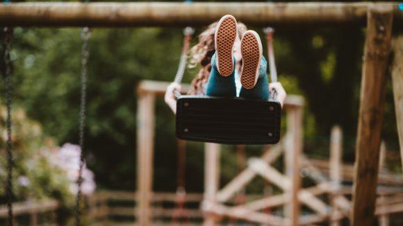 Kind auf Schaukel auf einem Spielplatz