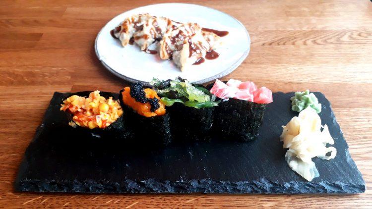 Schieferplatte mit Sushi vegan, gefüllt mit Kürbis, Algensalat, Soya und Maissalat und ein Teller mit Dumplings im Hintergrund