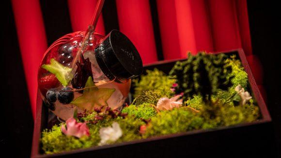 Cocktail in einem ruden Glas mit Blumen- und Grasdeko.