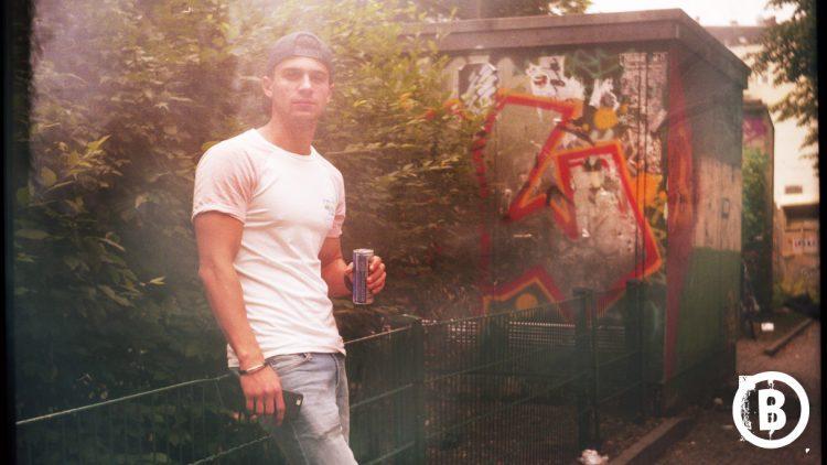 Junger Typ mit Cap und Energy-Drink in der Hand lehnt am Gartenzaun