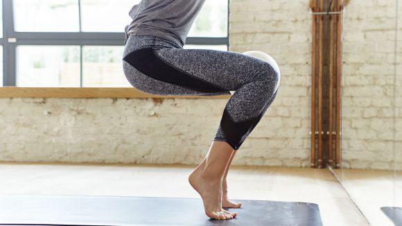 Unterkörper einer Frau beim Training mit Ball zwischen den Knien, auf Zehenspitzen