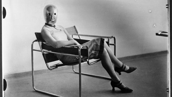 Frau mit kurzen Ärmeln, Rock und einer goldenen Maske sitzt in einem Breuersessel