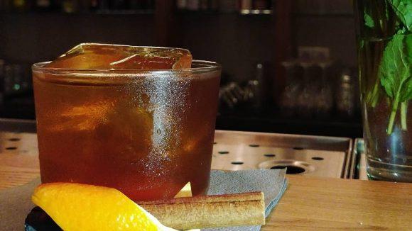 Cocktail auf einer Holz-Theke mit Zitrone und Zimt.