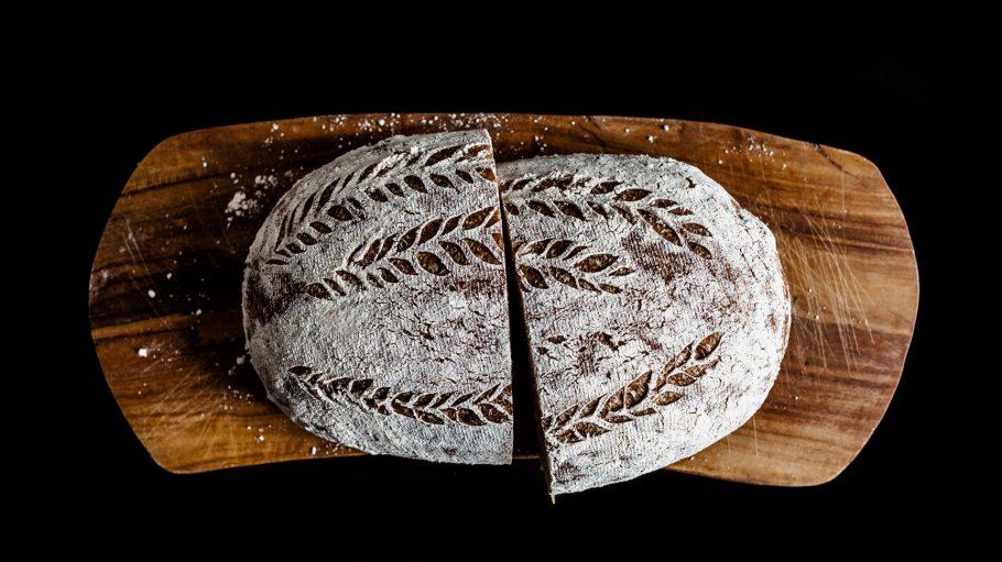 In zwei Hälften geschnittenes Sauerteigbrot mit Mustern auf einem Holzbrett
