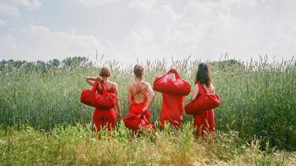 Vier Frauen in rot gekleidet und mit roten Taschen stehen mit dem Rücken zum Betrachter vor einem Feld.