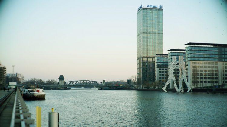 Fluss Spree, mit Elsenbrücke in der Ferne, rechts ein Hochhaus (Allianz Tower) und zwei Figuren in der Spree (Molecule Men)