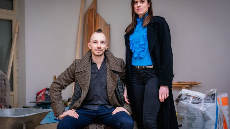 Das Pärchen Filip und Anastasia vor Brettern und eine Schubkarre.