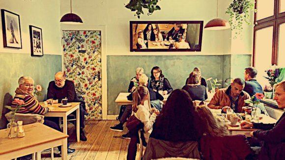 Café Daily Day gemütlich mit viel Holz, liebevoller Dekoration und schönen Blumen und Bildern im Raum.