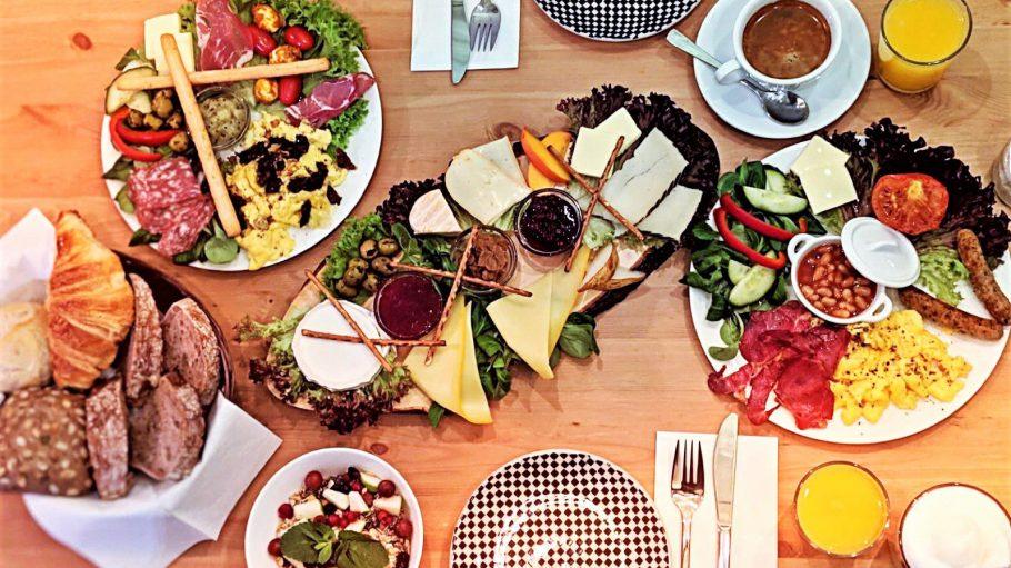 Frühstück im Daily Day Café in Schöneberg mit Käse, Wurst, Rührei, Bacon, Croissants, frisch gepresstem Saft auf einem Holztisch.