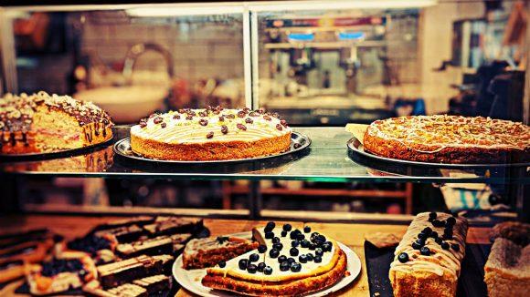 Kuchenvitrine im Daily Day in Schöneberg: vegane Kuchen mit Früchten und klassischer Cheesecake liegen hier zur Auswahl bereit.