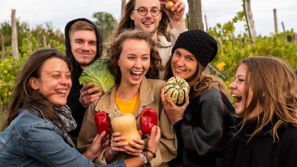 Die Genoss*innen von PlantAge stehen vor ihrem Acker und halten freudig lachend Gemüse ins Bild.