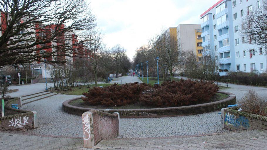 Promenade mit kahlen Kastanien und blauen Laternen zwischen Mietshaus-Neubauten