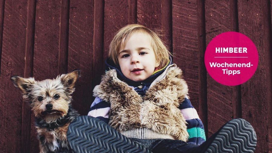 Kind und Hund sitzend vor einer Holzwand