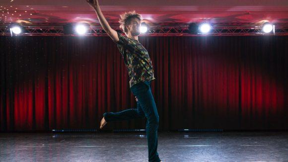 Tänzer auf einer Bühne mit rotem Vorhang im Hintergrund