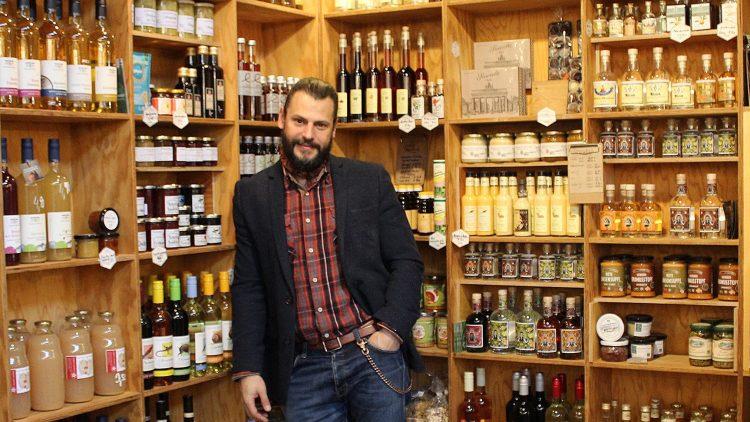 Manuel Cortez, bärtiger, dunkelhaariger Mann mit Jackett, Hemd und Jeans, lehnt an Regalen mit Flaschen und Marmelade
