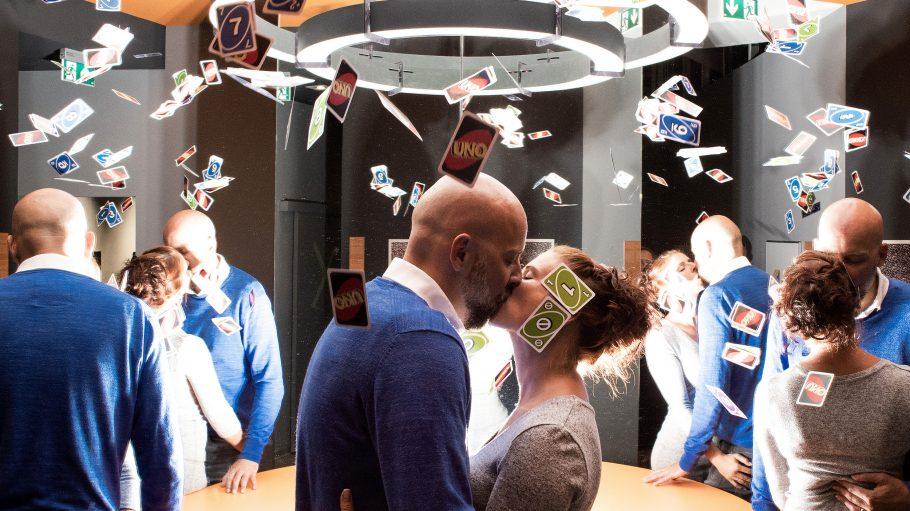 Ein küssendes Paar (Mann mit Bart, Frau mit hochgesteckten Haaren) steht in Raum und ist mehrfach von verschiedenen Seiten zu sehen. Über ihnen flattern Spielkarten