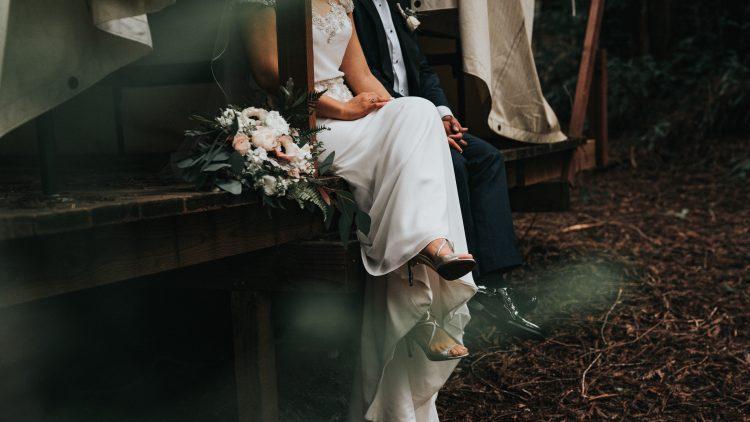 Hochzeitspaar sitzt mit Strauß im Wald in Berlin