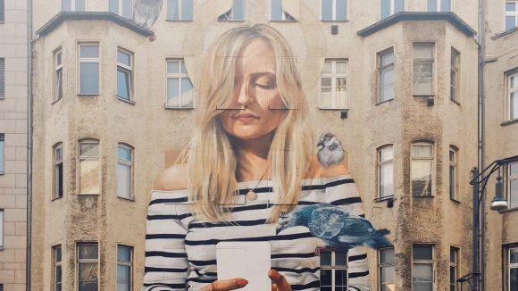 Mural: eine Frau blickt auf ihr Handy