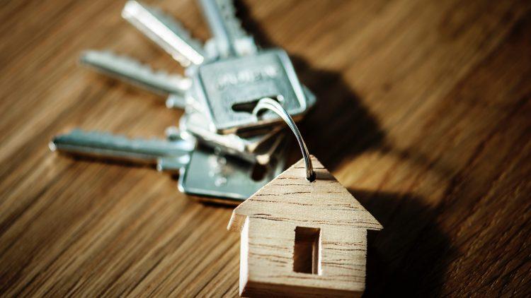 Ein Schlüsselbund mit einem Haus als Schlüsselanhänger auf einem Holztisch