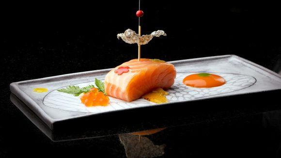Lachs mit Rogen und knuspriger Fischhaut, dekorativ angerichtet auf einem Teller