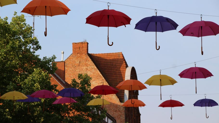 Bunte Regenschirme hängen an Seilen, im Hintergrund blauer Himmel und ein Haus