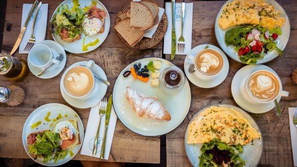 Fünf weiße Teller mit Lachstoast, Croissant oder Omelette und Salat auf Holztisch neben Milchkaffee und Brotscheiben