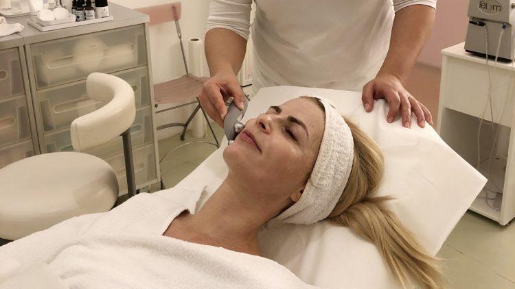 Frau mit Handtuch auf dem Kopf bekommt ein EMS-Training im Gesicht