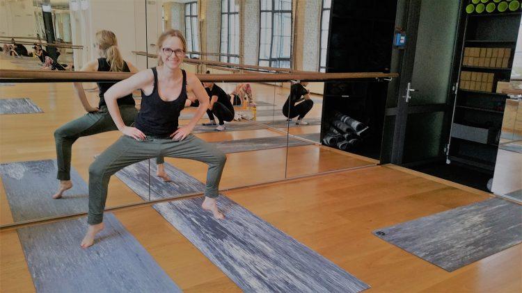 Frau mit Brille in Plié-Position auf Zehenspitzen im Yoga-Studio mit Barren
