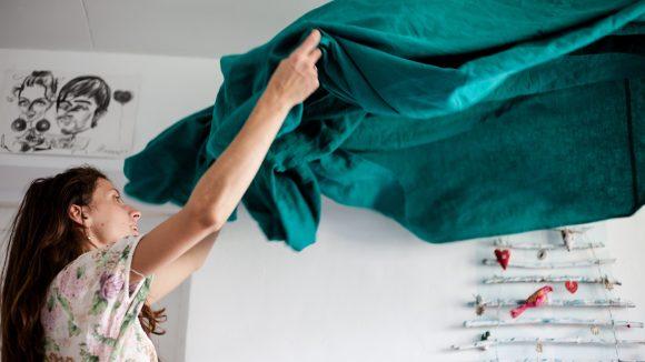 Frau mit roten Haaren, die eine grüne Decke beim Frühjahrsputz ausschüttlet.