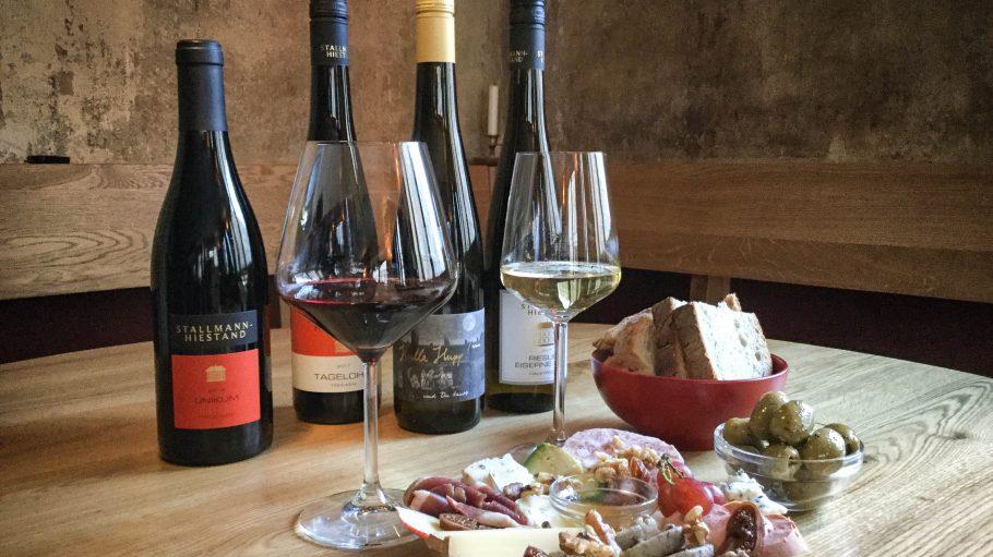 Verschiedene Weinflaschen auf einem Holztisch mit Tapastelle, Brot und Oliven