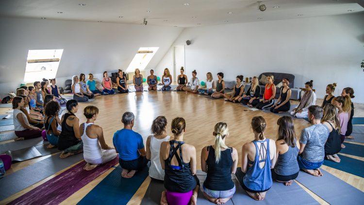 Menschen sitzen auf Yogamatten in einem Kreis.