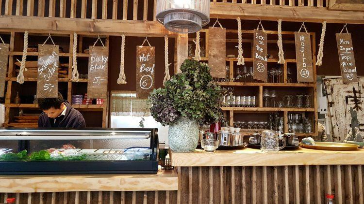Die Bar im Restaurant mit Schildern, die von der Decke hängen auf denen Gerichte und die Preise stehen