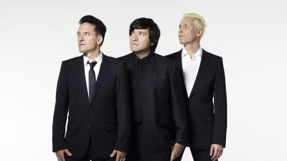 """Die Band """"Die Ärzte"""" im Anzug vor einer weißen Wand"""