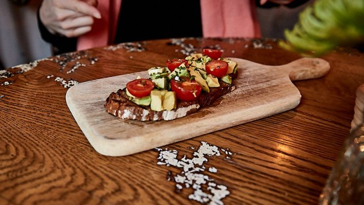 Ein Avocadobrot mit Tomanten auf einem Holzbrett.