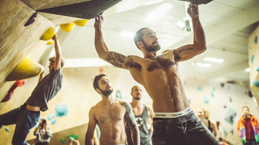 Männer mit freiem Oberkörper klettern in deiner Boulderhalle.