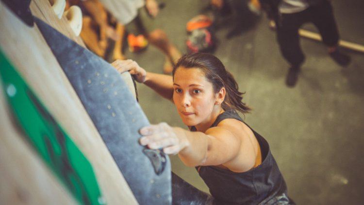 Frau mit dunklen Haaren klettert die Wand hoch.