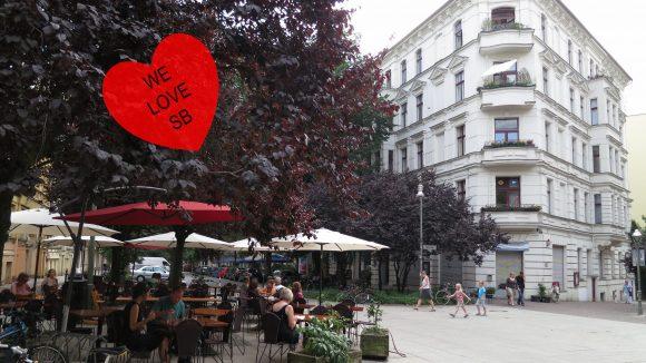 Blick auf den Crelleplatz mit Menschen, die in einem Café sitzen