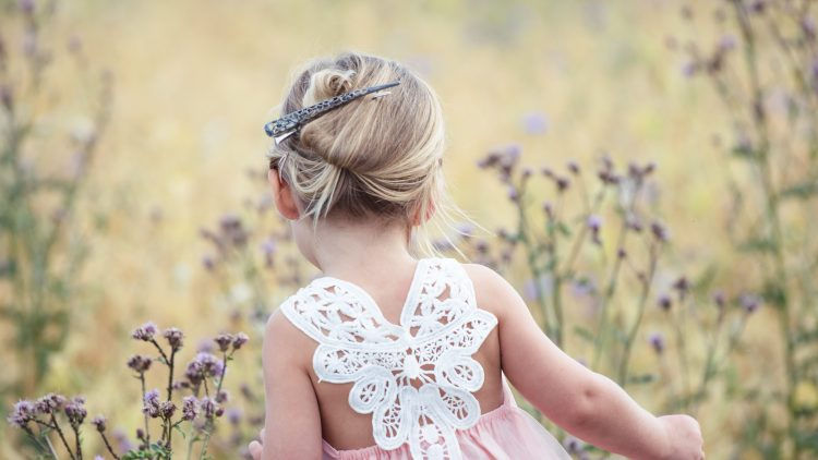 Kleines Mädchen mit Hochsteckfrisur auf einer Wiese