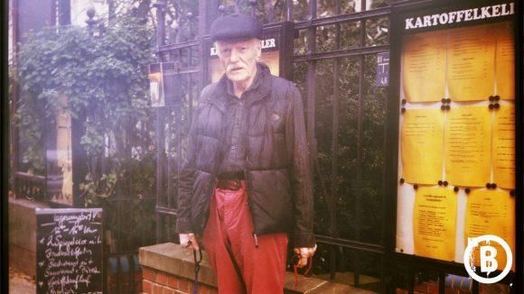 Der Gastronom Friedel steht mit roter Hose und schwarzer Lederjacke und Kippe vor einem Zaun.