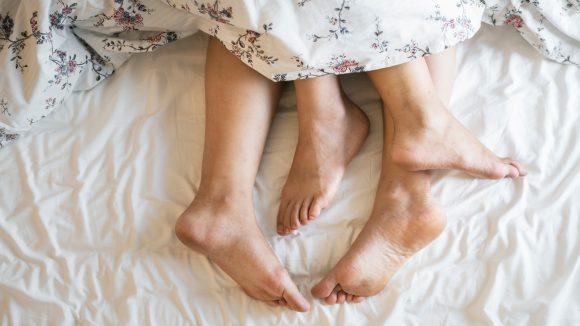Vier Füße schauen aus der Bettdecke hervor