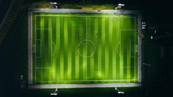 Fußballplatz vom Flutlicht erleuchtet aus großer Höhe
