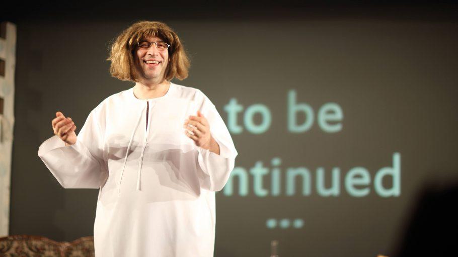 Ein Mann mit dunkelblonder Perücke und weißem Kleid steht auf einer Bühne: Oliver Tautorat