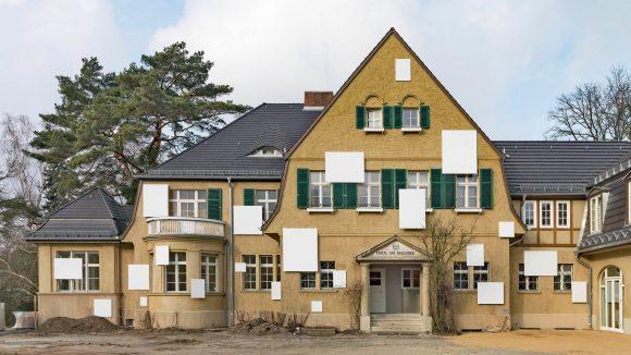 Beige Villa im englischen Landhausstil mit weißen Leinwänden an der Fassade und Lehmboden im Vordergrund: Haus am Waldsee, Berlin