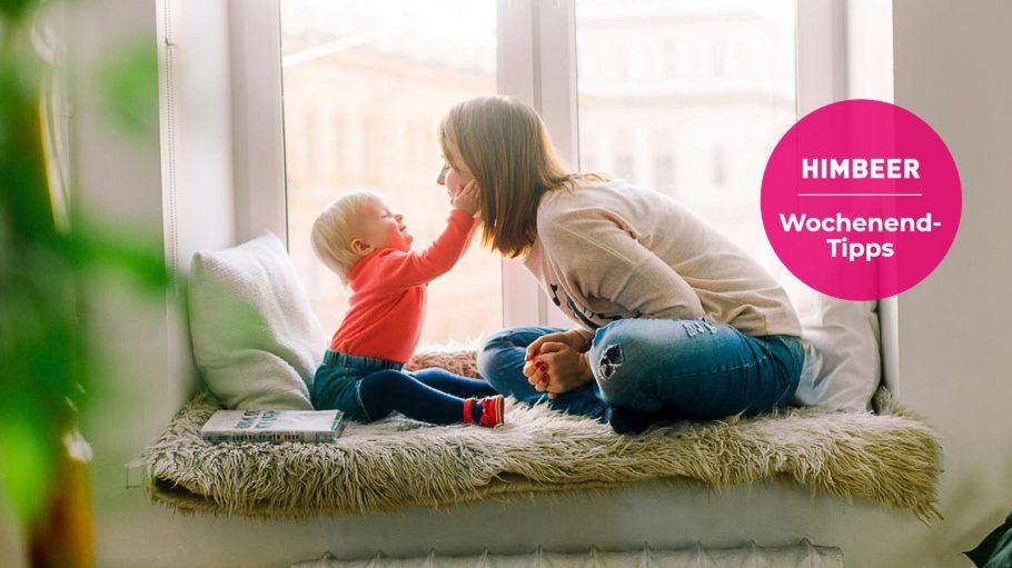 Frau und Kind sitzen auf einem Fensterbrett