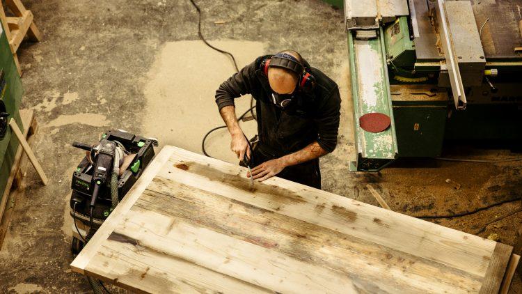 Mann mit Ohren- und Mundschutz arbeitet in einer Werkstatt mit Holz.