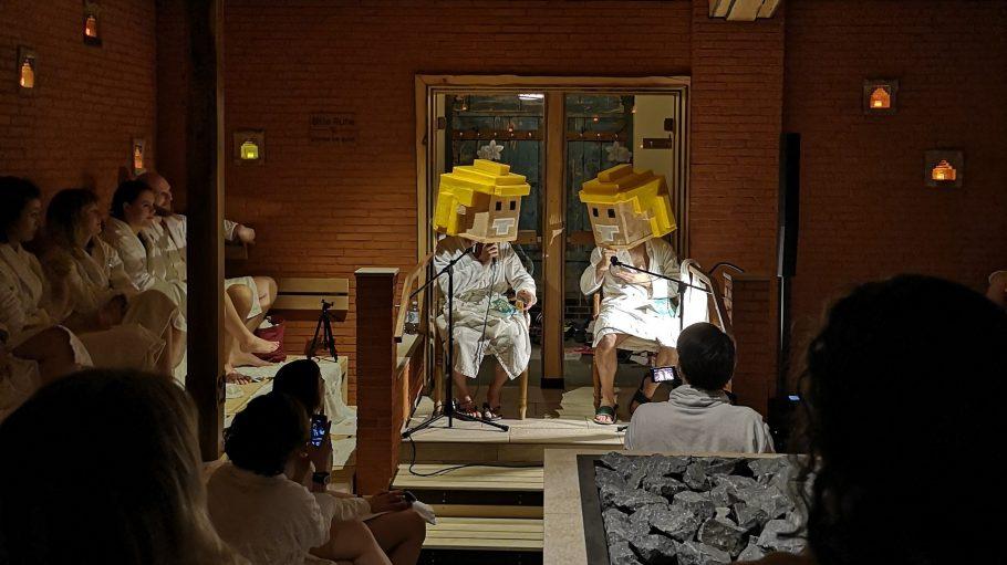 Menschen sitzen bei Buchlesung in Sauna