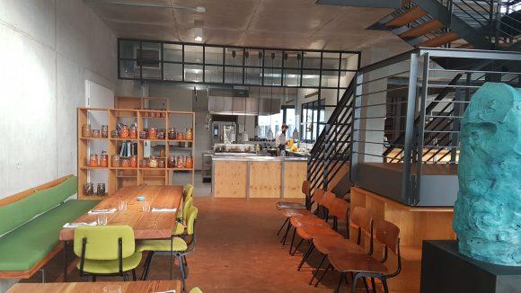 Der Innenraum der Bar Brass mit grünen Stühlen und schönen Holzmöbeln. Der Blick geht aus dem Gastraum nach hinten zur offenen Küche.