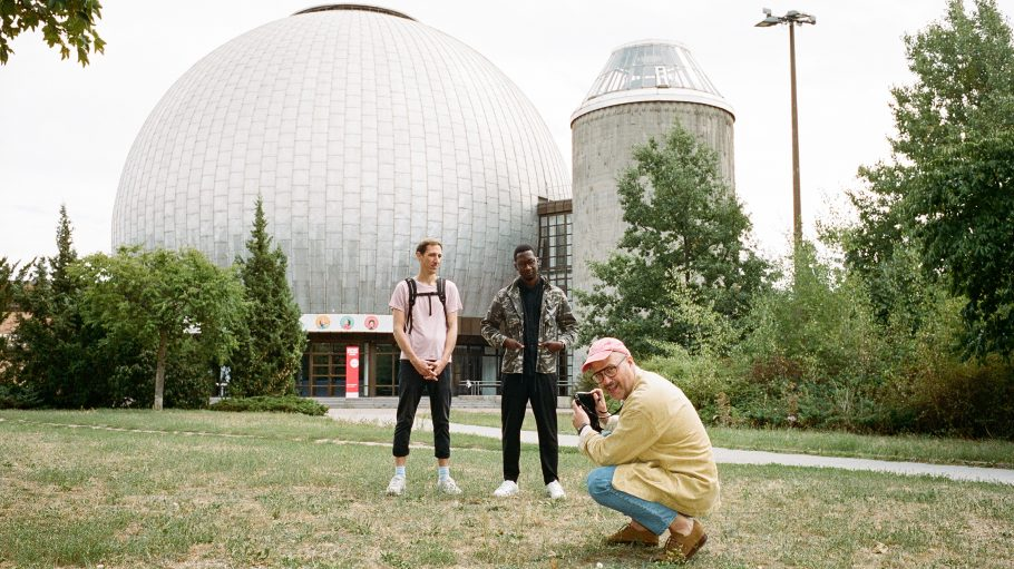 Zwei Männer stehen, einer mit Fotoapparat hockt im Park vor der Kugel des Zeiss-Planetariums in Berlin